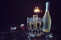 Partisammansättningsbild Exponeringsglas som fylls med champagne som förläggas på den svarta tabellen royaltyfri bild