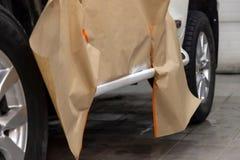 Partisk målning av de lägre beståndsdelarna av kroppen av en vit SUV bil efter skada, kroppen täckas med specialt papper och royaltyfri foto