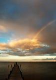 Partisk regnbåge över havet på aftonen Arkivfoto