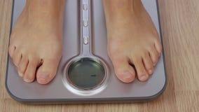 Partisk sikt av den barfota kvinnan som väger på elektronisk skala med skärm stock video