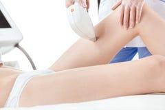 Partisk sikt av den unga kvinnan som mottar epilation för laser-hårborttagning på låret som isoleras på vit Arkivbilder