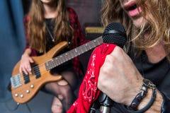 Partisk sikt av mannen som sjunger i mikrofon med kvinnan som spelar gitarren Arkivbild