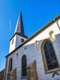 Partisk sikt för sida av den gamla kyrkan av St Lawrence i Diekirch, Luxembourg med en contrail i himlen royaltyfri foto