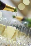 Partit buteljerar hällande champagne in i exponeringsglas Arkivbild