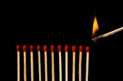 Partita bruciante con la fila delle partite isolate su fondo nero fotografia stock libera da diritti