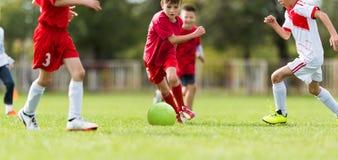 Partita di calcio dei giocatori dei bambini piccoli sul campo di calcio Fotografie Stock
