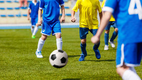 Partita di calcio di calcio Bambini che giocano calcio Young Boys che dà dei calci alla palla di calcio sul campo sportivo Fotografie Stock Libere da Diritti