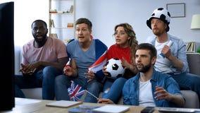 Partita di calcio di sorveglianza di fan britannici multietnici a casa, sostenendo gruppo fotografie stock libere da diritti