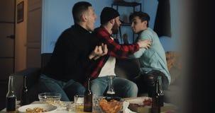 Partita di calcio di sorveglianza di tre amici sulla TV a casa, incoraggiando migliore squadra di calcio emozione I fan degli uom video d archivio