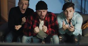 Partita di calcio di sorveglianza di tre amici sulla TV a casa, incoraggiando migliore squadra di calcio emozione I fan degli uom archivi video