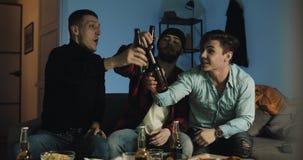 Partita di calcio di sorveglianza di tre amici sulla TV a casa, incoraggiando migliore squadra di calcio emozione I fan degli uom stock footage
