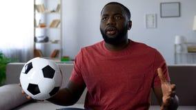 Partita di football americano di sorveglianza dell'uomo afroamericano a casa, insoddisfatto del punteggio della partita fotografia stock