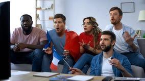 Partita di sorveglianza degli amici francesi sulla TV a casa, sostenendo squadra di football americano favorita immagini stock
