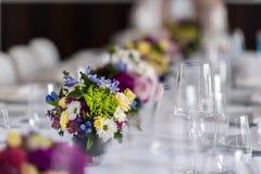 Partitabell med exponeringsglas och blommor arkivbilder