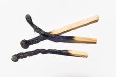 Partite bruciate isolate sul primo piano bianco del fondo Fotografia Stock Libera da Diritti
