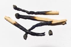 Partite bruciate isolate sul primo piano bianco del fondo Fotografie Stock Libere da Diritti