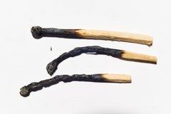 Partite bruciate isolate sul primo piano bianco del fondo Fotografia Stock