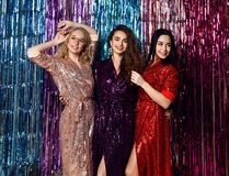 Partitid av tre härliga stilfulla kvinnor i elegant dräkt som firar det nya året, födelsedag och att ha gyckel, dans arkivfoto