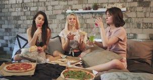 Partitid för damer hemma som äter pizza och dricker en flaska av några drinkar som utmärkt känner sig, bära pyjamas och arkivfilmer