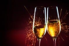 Partitid för nytt år med två champagneexponeringsglas och tomteblossaga Arkivbild