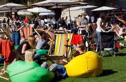 Partito ammucchiato con la gente di rilassamento sotto gli ombrelli ad area verde del salotto Fotografia Stock Libera da Diritti