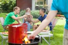 Partito con il barbecue in un giardino Fotografie Stock Libere da Diritti