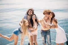 Partito dell'yacht con i giovani che hanno un partito della barca, ballante su una prua della piattaforma dell'yacht immagine stock