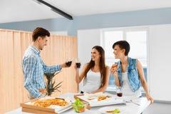 Partito di cena Amici felici che mangiano pizza, divertendosi Amicizia Fotografie Stock