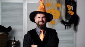 Partito di Halloween e mago divertente Musica di notte Cappello magico L'uomo barbuto in un cappello arancio alza le sopracciglia stock footage