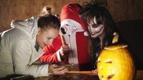 Partito di Halloween, notte, penombra, nei raggi di luce, di un tipo vestito come Santa diabolica e di una donna con un terribile archivi video