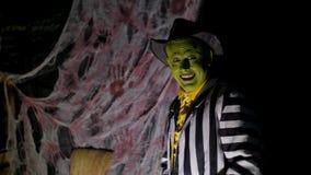 Partito di Halloween, notte, penombra, nei raggi di luce, di un uomo con un trucco terribile, con un fronte verde e un cappello archivi video