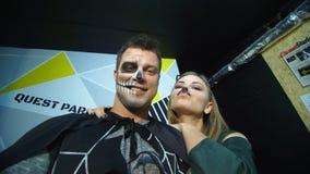 Partito di Halloween, notte, ritratto spaventoso di un uomo con un trucco terribile in un costume nero e una ragazza in un gatto stock footage