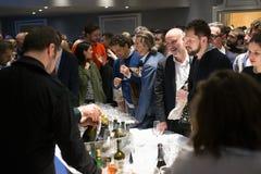 Partito di sera con le folle delle persone di sesso maschile bianche alla barra di banchetto che ha bevande Immagine Stock