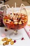 Partito di sungria della frutta grande vetro, lotti delle paglie sulla tavola Immagine Stock