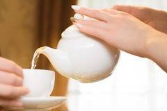 Partito di tè Le donne versano il tè verde in una tazza bianca fotografie stock