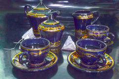 Partito di tè Tè in tazze, insiemi di tè e bustine di tè su un fondo nero Fotografia Stock