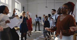 Partito felice di celebrazione di risultato all'ufficio multietnico moderno La diversa gente di affari balla nel luogo di lavoro  archivi video