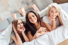 Partito Giovani donne che si trovano insieme sul primo piano allegro sorridente del letto a casa fotografie stock