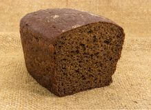 Partly cut brown rye and wheat bread on a sackcloth. Half of loaf of the brown rye and wheat bread with added rye malt and coriander on a sackcloth royalty free stock image