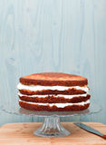 Partly frosted cake on a glass stand, decoration in a process Royalty Free Stock Image