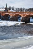 Partly frozen river that passes through a very old, brick-built bridge. Sunny winter day in nature, everything is white with snow; there is a partly frozen river Royalty Free Stock Image