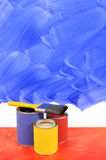 Home renovation - unfinished painted blue wall, paint cans, paintbrush, copy space, vertical Royalty Free Stock Image