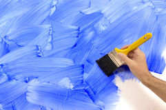 Man painting wall, holding paintbrush, blue paint, copy space Stock Photos