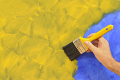 Home repairs - man holding paintbrush painting wall, copy space Royalty Free Stock Photo