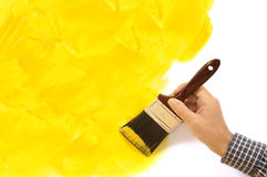 House painting and decorating - unfinished painted yellow wall with man holding paintbrush.  Copy space. Royalty Free Stock Photos