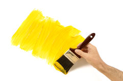 Home repairs : unfinished partly painted yellow wall, man holding paintbrush.  Copy space. Stock Photo