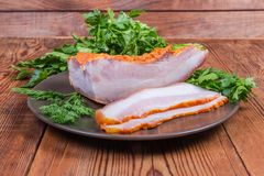 Partly sliced boiled smoked pork belly on dish with greens. Partly sliced boiled smoked pork belly with rind on the brown dish with greens on the wooden rustic royalty free stock photography