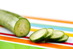 Partly sliced organic cucumber on a stripy colorful ceramic plate Stock Photos