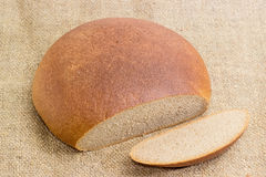 Partly sliced wheat rye hearth bread on a sackcloth Royalty Free Stock Photography