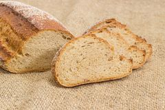 Brown bread with whole sprouted wheat grains on sackcloth closeu. Partly sliced wheat and rye sprouted bread with added whole sprouted wheat grains, rye malt and Royalty Free Stock Photo